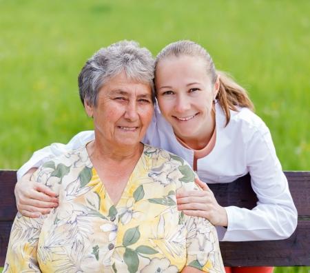reassurance: Mujer mayor con su cuidadora en la naturaleza Foto de archivo
