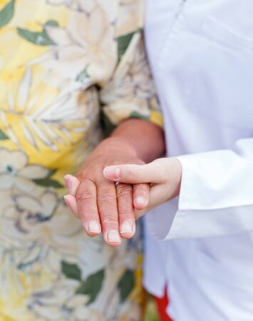Young doctor holds the elderly woman hands Stock Photo - 19832586