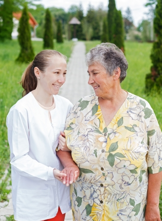 assisting: Elderly woman with her caretaker walking in the nature