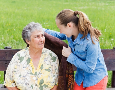 Young girl wrap her mother with a warm sweater