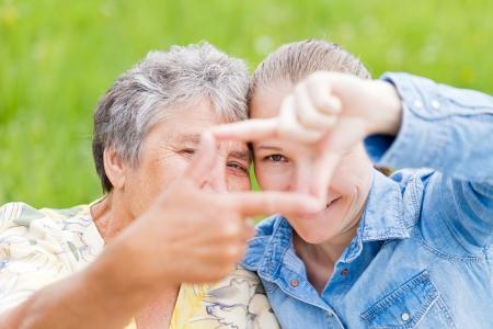 Une femme âgée et sa fille encadrant leurs visages