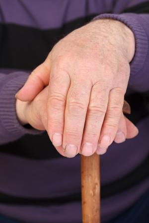 Old mans worker hand resting on the walking stick photo