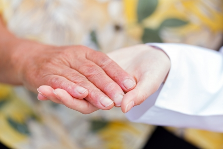 Young doctor holds the elderly woman hands Stock Photo - 22665184
