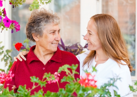 aide: Happy elderly woman and her helpful assistant Stock Photo