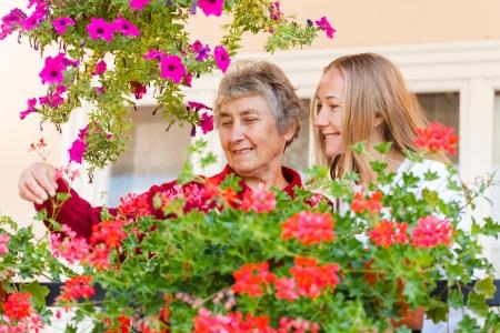 年配の女性は、彼女のアシスタントの彼女の花