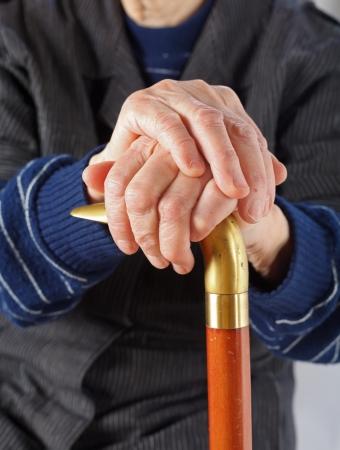 rheumatoid: Elderly hands resting on the walking stick Stock Photo