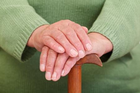 Alte Frau, die Hände ruhen auf dem Spazierstock