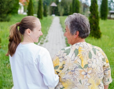 Elderly woman with her caretaker walking in the nature
