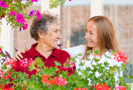 Happy elderly woman and her helpful assistant Stock Photo