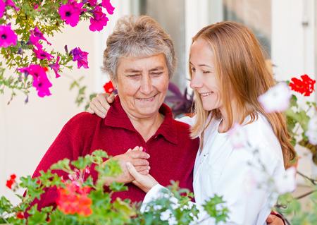 vejez feliz: Mujer mayor feliz y su asistente útil Foto de archivo