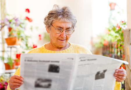Elderly woman sitting on the veranda and reading newspaper  Stock Photo - 23309583