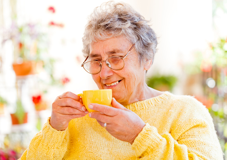 Elderly woman sitting on the veranda and drinking coffe Stock Photo - 23309591