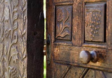 puerta abierta: Abrir la puerta de madera con motivos florales tallados