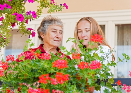 Elderly woman shows her flowers to her assistant Stock Photo