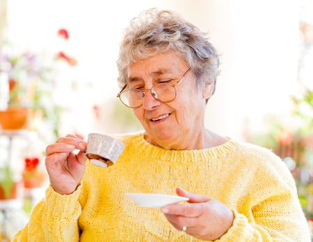 Elderly woman sitting on the veranda and drinking coffe photo
