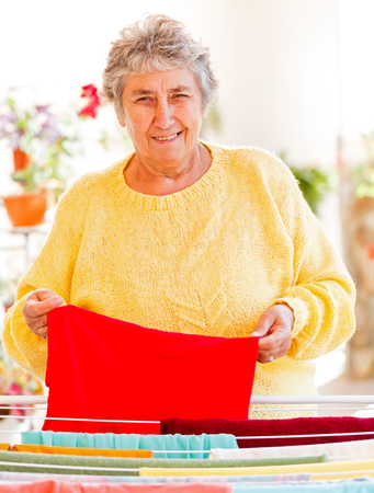 Elderly woman put the wet clothes on the dryer photo