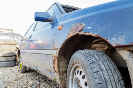 salvage yard: Side view of an old fashioned car in a junkyard