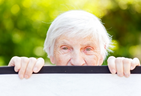 Portrait of the smiling elderly woman on outdoors Stock Photo