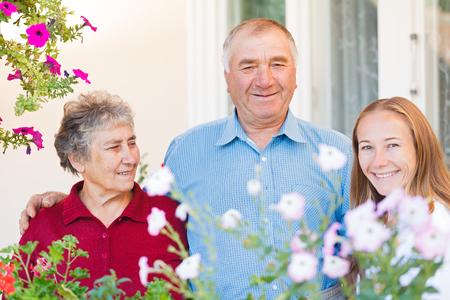 apoyo familiar: La pareja de ancianos felices con su cuidador Foto de archivo