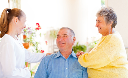 carer: Happy elderly couple talking with their carer