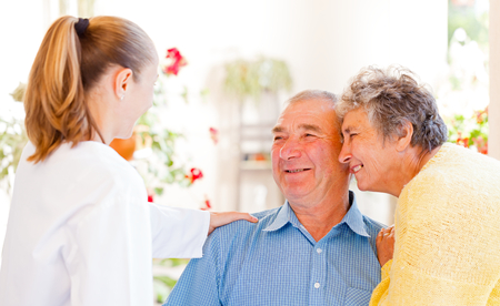 Happy elderly couple talking with their carer photo