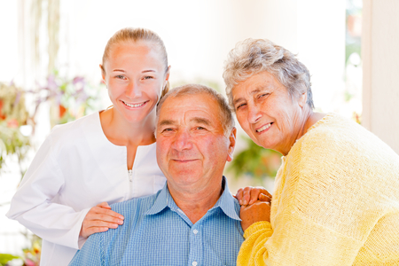 nursing aid: Happy elderly couple talking with their carer