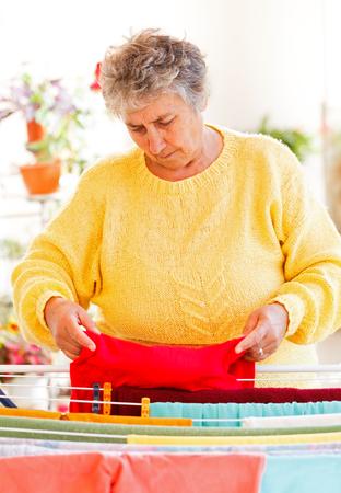 wet clothes: Anciana poner la ropa mojada en la secadora