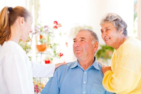 Feliz pareja de ancianos hablar con su cuidador