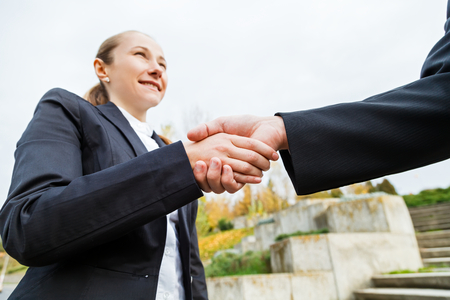 copartnership: Young businesswoman shaking hands with her partner