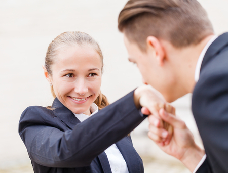 Young businessman greet polite his partner with kissing hand
