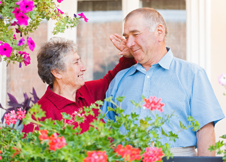 caresses: The happy elderly woman caresses her hausband Stock Photo