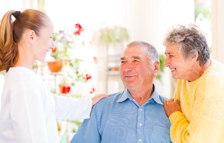 pacientes: Feliz pareja de ancianos hablar con su cuidador