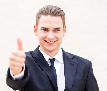 Young attractive successful businessman shows thumbs up photo