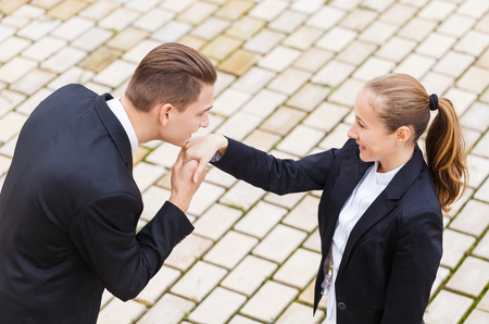 polite: Young businessman greet polite his partner with kissing hand