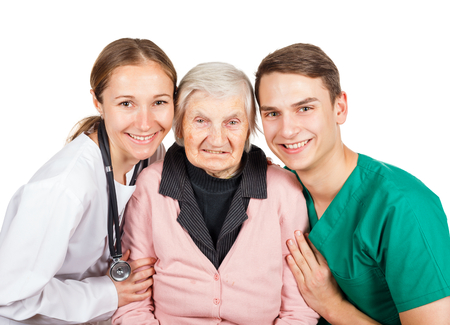 carers: The elderly woman with her helpful caregivers Stock Photo