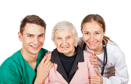 hospice: The elderly woman with her helpful caregivers Stock Photo