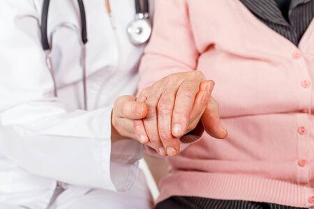 Giovane medico che dà aiutando le mani per la donna anziana