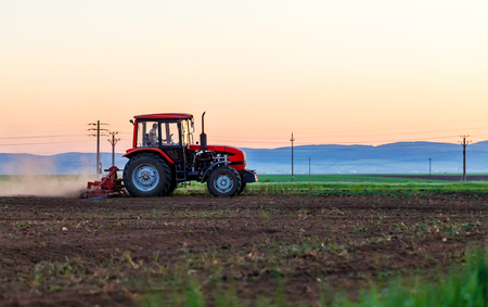 plowed field: Agricultural work a tractor ploughing the field Stock Photo
