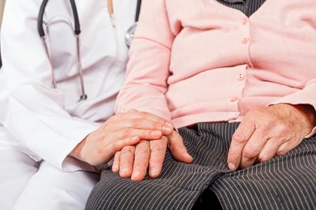 Giovane medico che dà mani che aiutano per la donna anziana