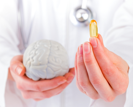 Closeup photo of doctor holding omega 3 capsule in hand Standard-Bild