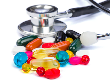 adjuvant: Closeup photo of colorful pills and stethoscope on  isolated white background