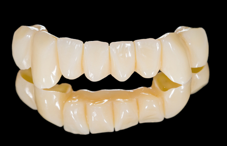 esthetics: Ceramic front bridge on isolated black background