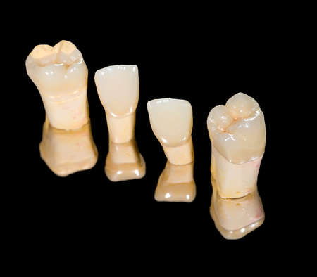 incisor: Dental ceramic crowns on isolated black background Stock Photo