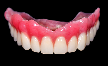 The artificial denture on isolated  black background