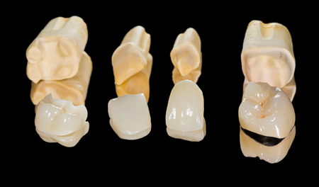 Dental ceramic crowns on isolated black background Archivio Fotografico