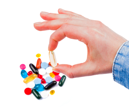 adjuvant: Closeup photo of colorful pills in hand on isolated white