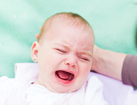 angry baby: Portrait of a crying baby because she is teething