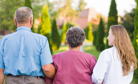 Elderly couple walking in the nature with the carer
