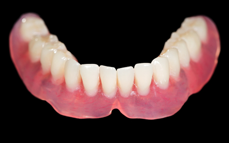 prosthodontics: Artificial lower denture on isolated  black background Stock Photo