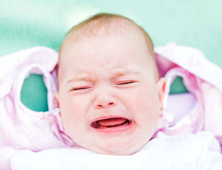 grouchy: Portrait of a crying baby because she is teething